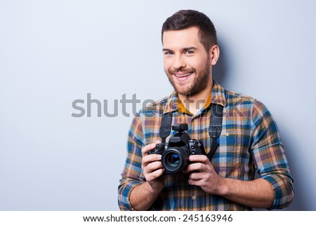 Expert in photography. Portrait of confident young man in shirt holding camera while standing against grey background - stock photo