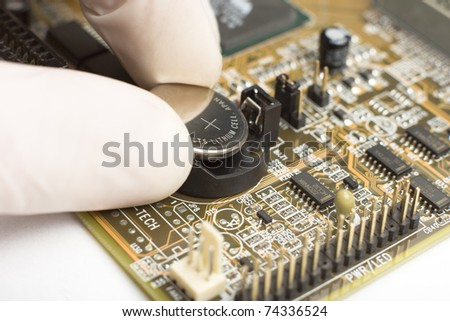 expert in white mitten on hand is putting round reflective battery with plus sign into computer motherboard - stock photo