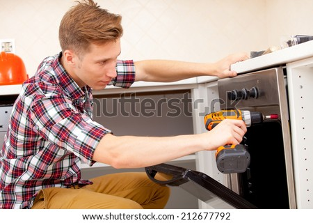 expert panel fixing the kitchen oven in a new apartment - stock photo