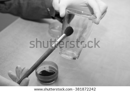 Expert takes fingerprints from a glass - stock photo