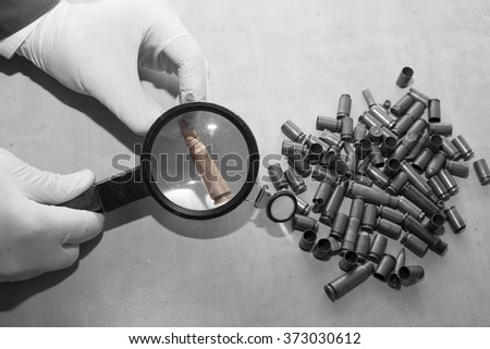 expert through a magnifying glass looking at a bullet at the cri - stock photo