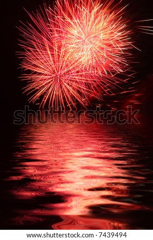 Exploding colorful fireworks against a night sky reflected in water - stock photo