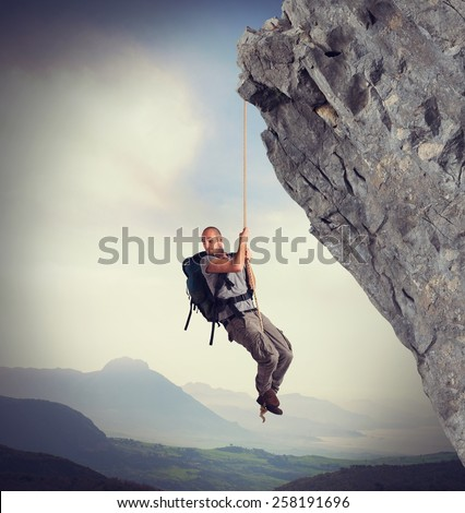 Explorer frightened by height scale the mountain - stock photo