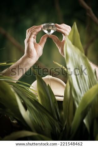 Explorer in the jungle finding a huge precious diamond. - stock photo