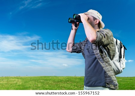 Explorer looking through binoculars outdoors - stock photo