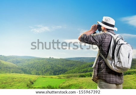 Explorer watching nature through binoculars