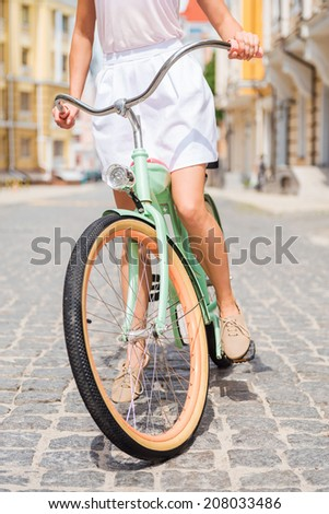 Exploring town by bike. Close-up of young woman riding bicycle along the street - stock photo