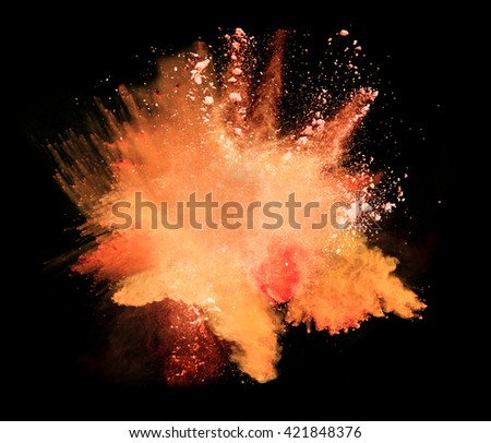Explosion of orange powder on black background - stock photo