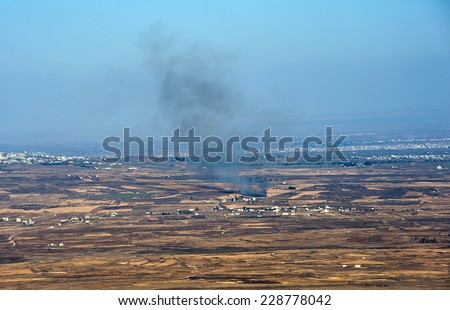 Explosions from the war in Syria can be seen from a hill on the Golan Heights 150 meter from the border, about 10 kilometers south/south-east of the city of Al Quneitra, October 04, 2014 in Israel - stock photo