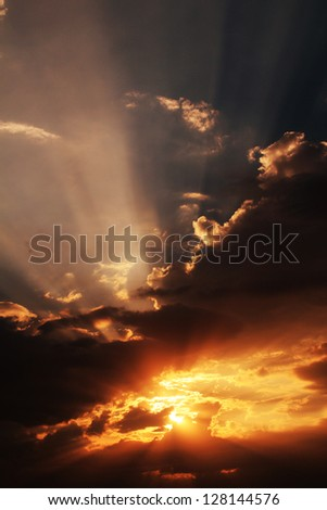 Explosive epic sun beams trough cloud - stock photo