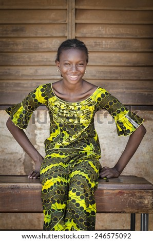 Expressing Positivity: Sitting Gorgeous African Girl Huge Smile On Desk - stock photo