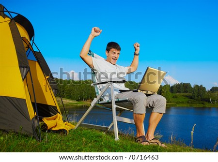 expression portrait of succesful man with laptop sitting in folding chair near camp tent outdoors