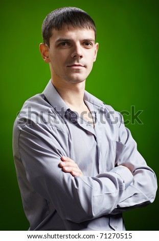 expression portrait of young handsome brunet guy posing in gray shirt on green - stock photo