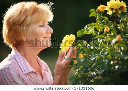 Expression. Senior Woman Model with Garden Roses. Springtime - stock photo