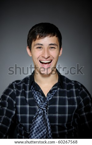 Expressions Handsome man in funny shirt and tie laughing - stock photo