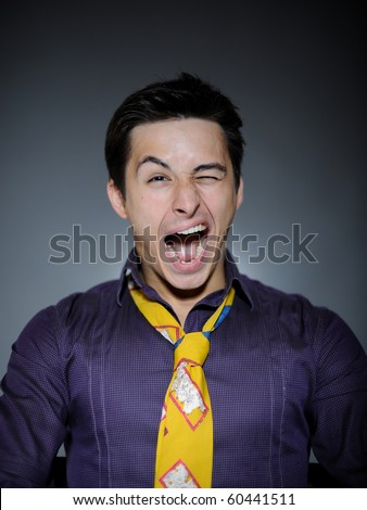 Expressions Handsome man in funny shirt and tie laughing and wink - stock photo