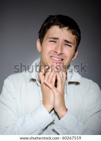 Expressions. Handsome young man feeling fear and crying - stock photo