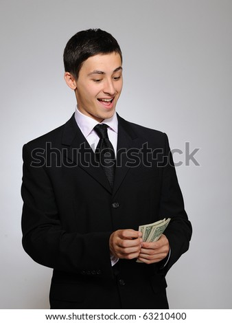 Expressions - Young handsome business man in black suit and tie counting money. gray background - stock photo