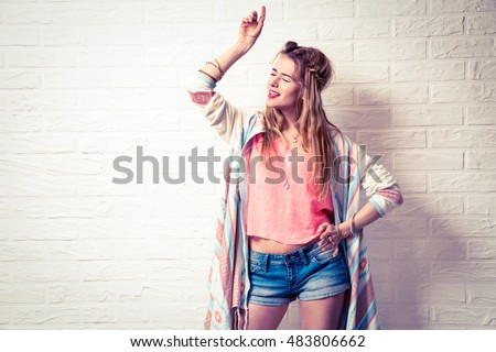 Expressive Boho Girl Singing and Dancing. White Brick Wall Background. Trendy Casual Fashion Outfit. Vintage Toned Photo with Copy Space.