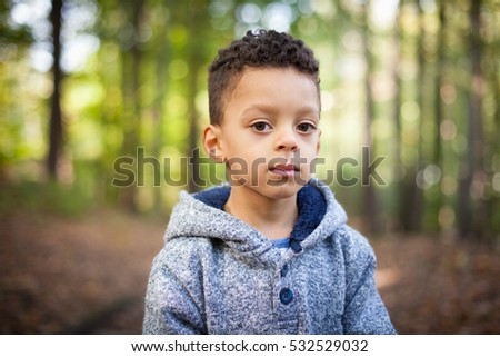 Expressive close up portrait of little mixed race boy - thoughtful