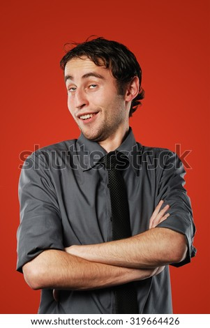 Expressive comic conceited young man isolated on red background - stock photo