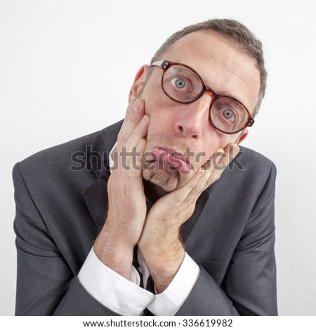 expressive corporate man concept - upset middle age businessman making a face,pressing his cheeks with both hands down,wide angle on white background - stock photo