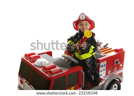 Expressive cute toddler with fireman's outfit on a fire truck - stock photo