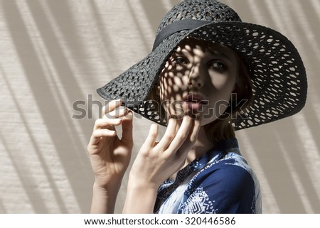 Expressive fashion close-up shoot of beautiful woman with romantic expression posing with lovely hat and her visage is in half-light.  - stock photo