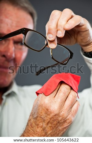 Expressive good looking senior man against grey wall. Cleaning his glasses. Funny and characteristic. Well dressed. Studio shot. - stock photo