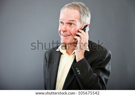 Expressive good looking senior man in dark suit against grey wall. Calling with cell phone. Funny and characteristic. Well dressed. Studio shot. - stock photo