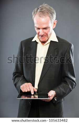 Expressive good looking senior man in dark suit against grey wall. Using tablet. Funny and characteristic. Well dressed. Studio shot. - stock photo