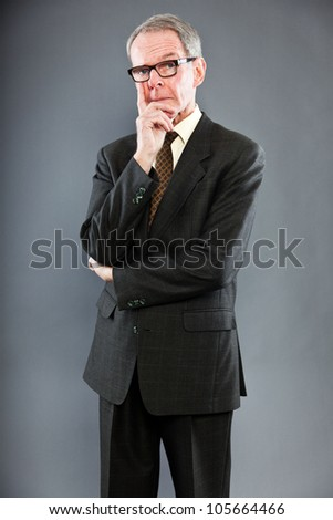 Expressive good looking senior man in dark suit against grey wall. Wearing glasses. Funny and characteristic. Well dressed. Studio shot. - stock photo