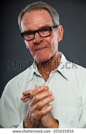 Expressive good looking senior man with glasses against grey wall. Hands praying. Spiritual and characteristic. Well dressed. Studio shot. - stock photo