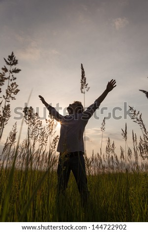 Expressive happy man with hands up on sunset background. - stock photo
