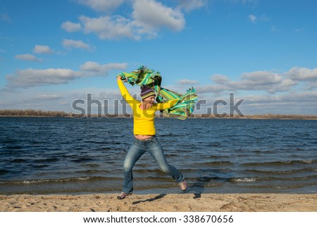 Expressive joyful  woman having fun, jumping with a veil in the wind, in the beach. Beautiful autumn day. - stock photo