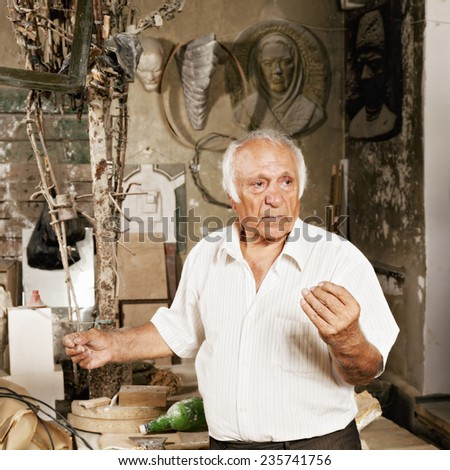 Expressive man gesturing while standing at sculptor workshop - stock photo