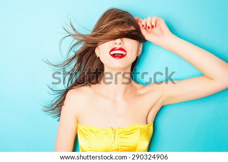 Expressive portrait of a beautiful young brunette woman in the studio on a blue background, the concept of beauty - stock photo