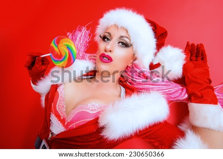 Expressive sexual girl in Santa Claus costume posing with lollipop over red background. Christmas.