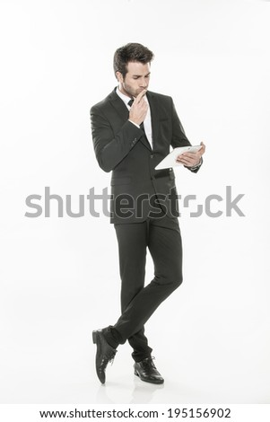 expressive young businessman in a suit using a digital tablet on isolated background - stock photo