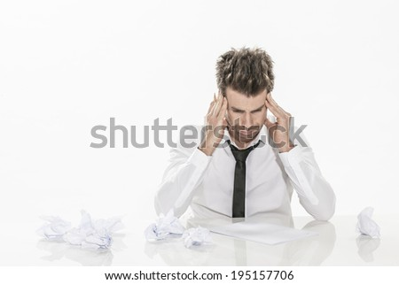 expressive young businessman sitting in front of a sheet of paper and a pencil and a few drafts on the table