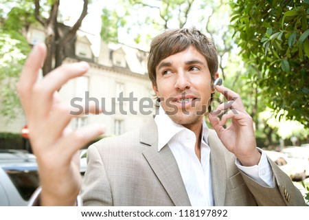 Expressive young businessman using an ear piece device and having a lively cell phone conversation while using his hands to gesture. - stock photo