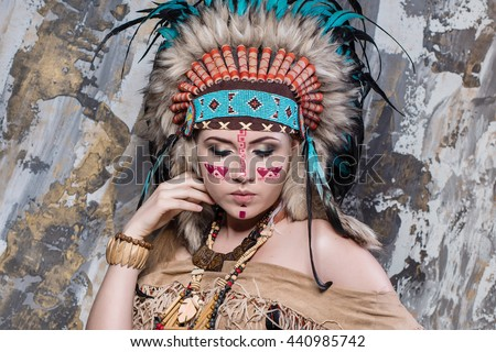 Expressive young girl with a pattern on the face and feathers and Roach looks directly into ethnic national style North American Indian background hairstyle and makeup close-up portrait - stock photo