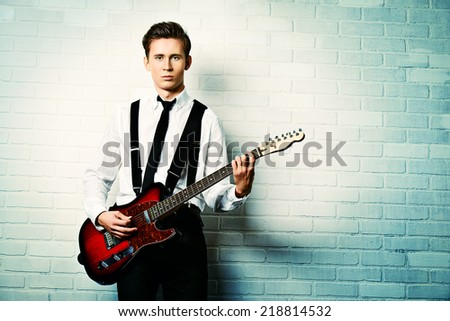 Expressive young man playing rock-n-roll music on his electric guitar. Retro, vintage style.  - stock photo