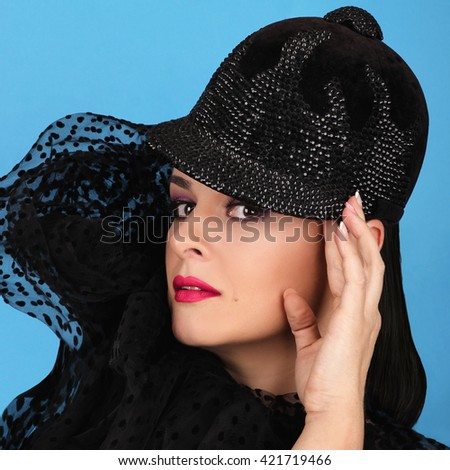 Expressive young model with black ridding cap for horse riders. Girl wearing fashionable hat. Model wearing the modern, fashion equestrian helmet. Perfect skin and fashionable make-up.