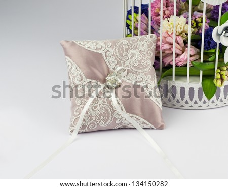 Exquisite pillow for wedding rings on gray background - stock photo