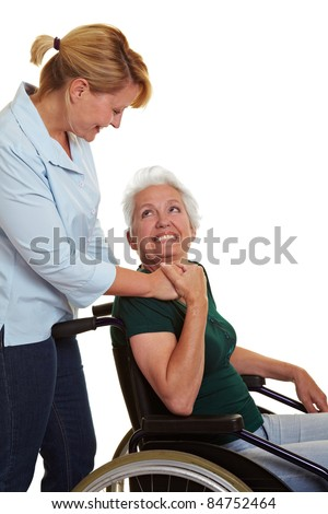 Extended care nurse helping disabled senior woman in wheelchair - stock photo