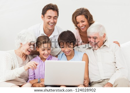 Extended family all looking at laptop on the couch - stock photo