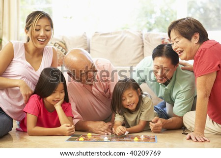 Extended Family Group Playing Board Game At Home - stock photo