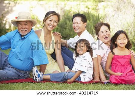 Extended Family Group Relaxing In Garden - stock photo
