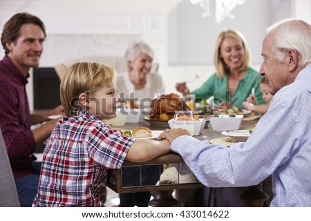 Extended Family Group Sit Around Table Eating Meal At Home - stock photo